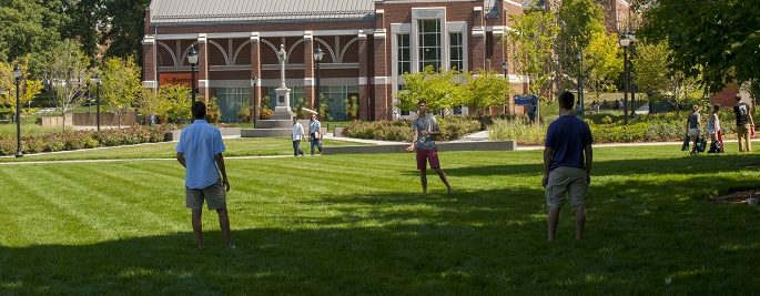 Students playing frisbee outside