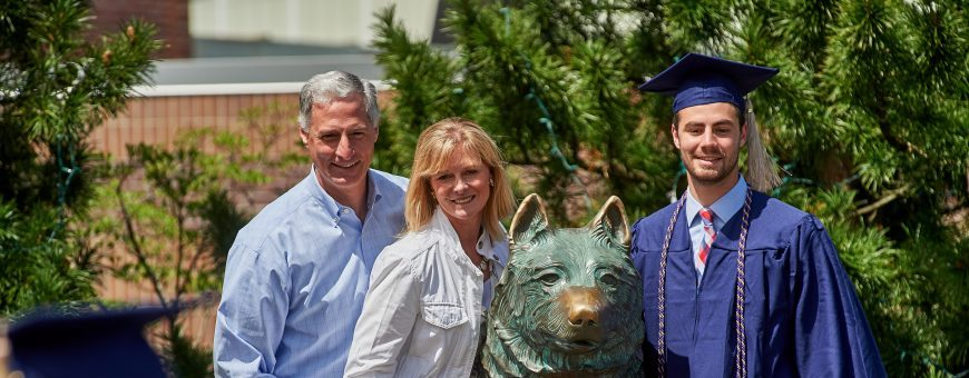 Andrew Patason '17 (BUS) poses for a photo at the husky statue with his parents Denise Patason '86 (BUS) and Andy Patason '86 (BUS) following the School of Business Commencement ceremony on May 7, 2017. (Peter Morenus/UConn Photo)