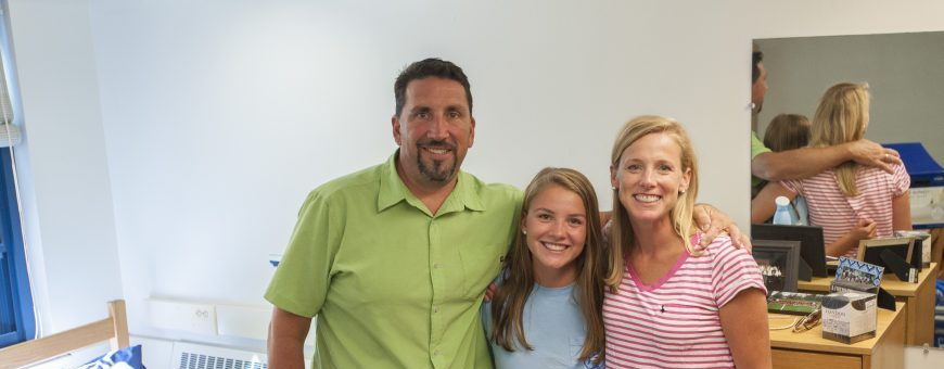 Daughter stands between parents inside residence hall room
