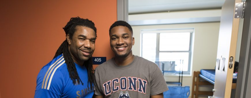 Father stands with son in front of residence hall room